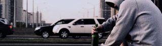 Combate às drogas - homem aparentemente alcoolizado sentado em via pública, com vários carros passando na via.