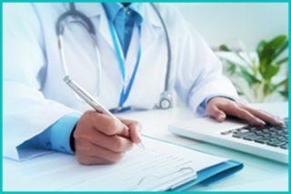 Provisa Gestão de Saúde: Médico escrevendo a receita para o paciente e com uma das mãos em frente do computador.
