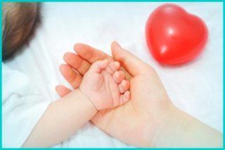 Provisa Gestão de Saúde: Mãe de bebê colocando a mão do seu filho em cima da sua mão com um coração bonito vermelho em cima da cama
